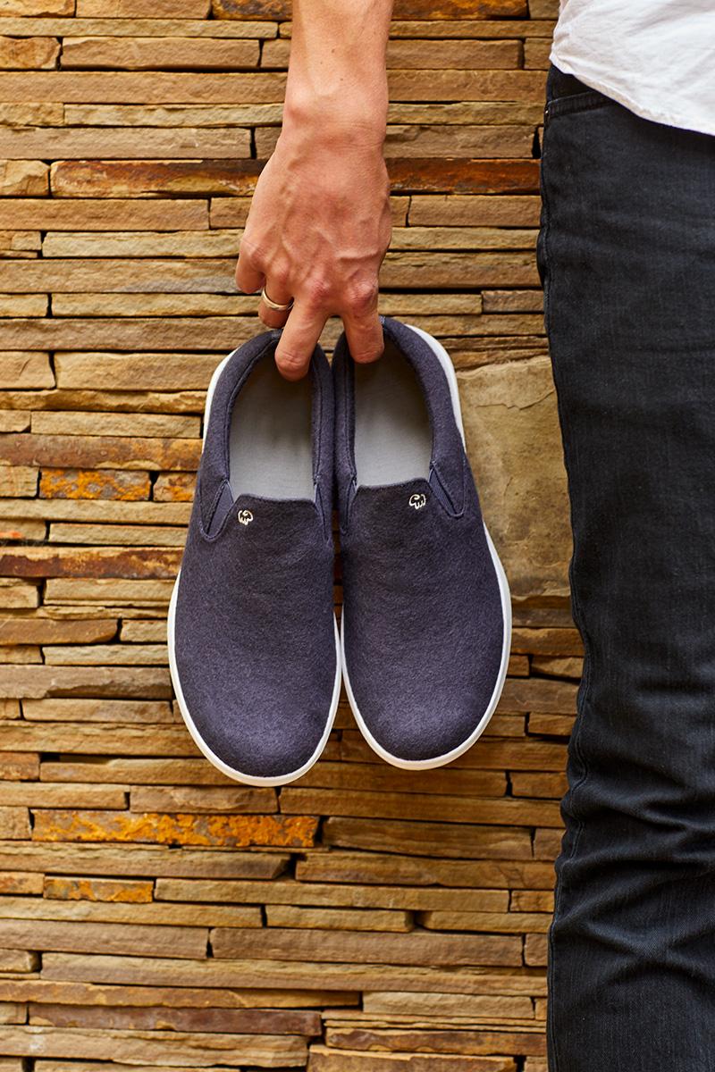 Mann hält blaue Schuhe in der Hand