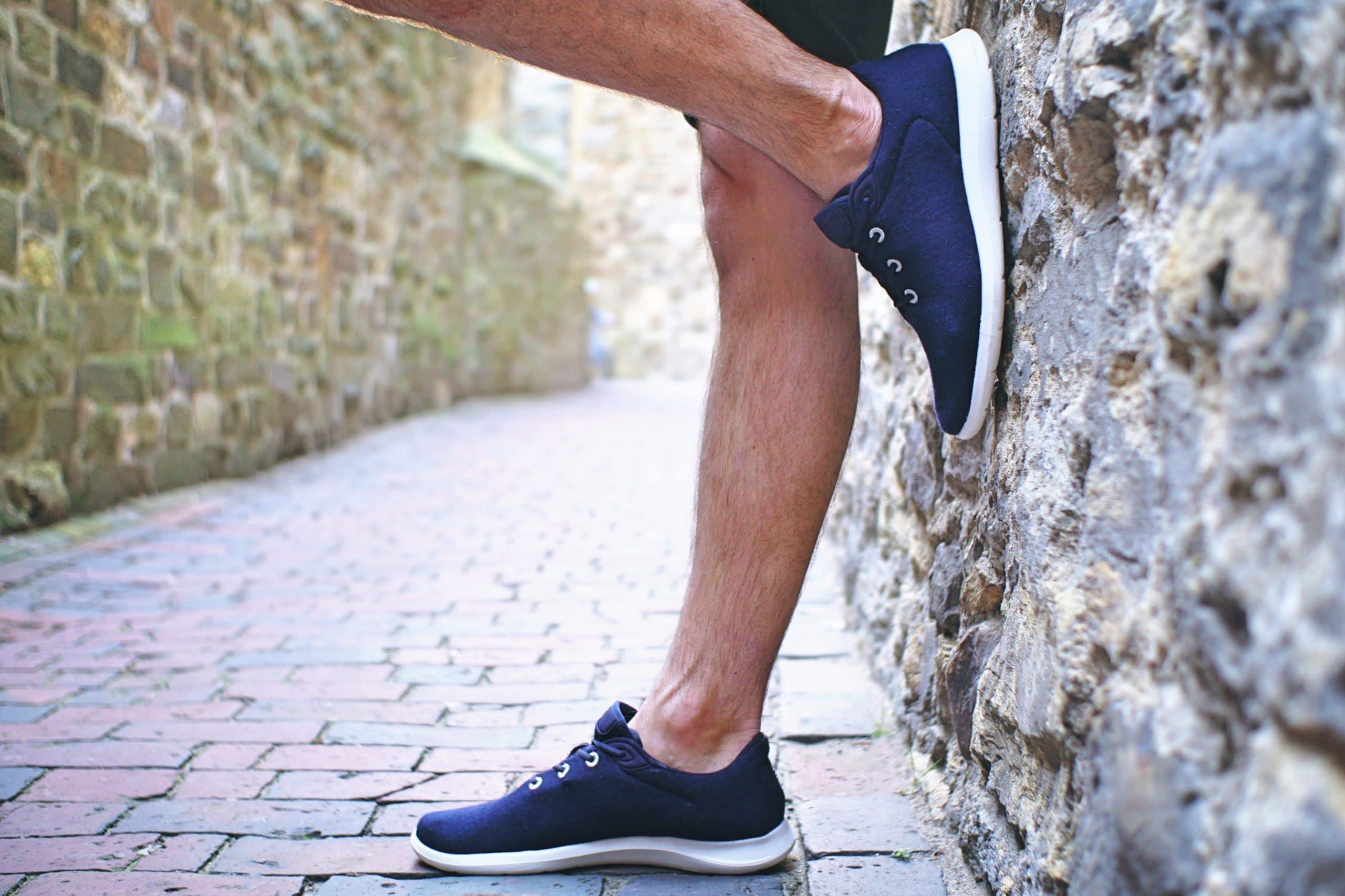 Mann mit blauen Schuhe lehnt an einer Wand
